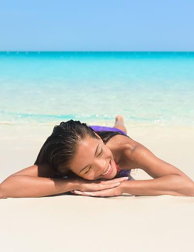 Woman relaxing on Grace Bay Beach