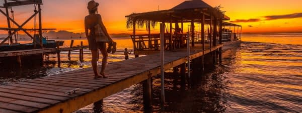 Woman on a pier in Roatan at sunset